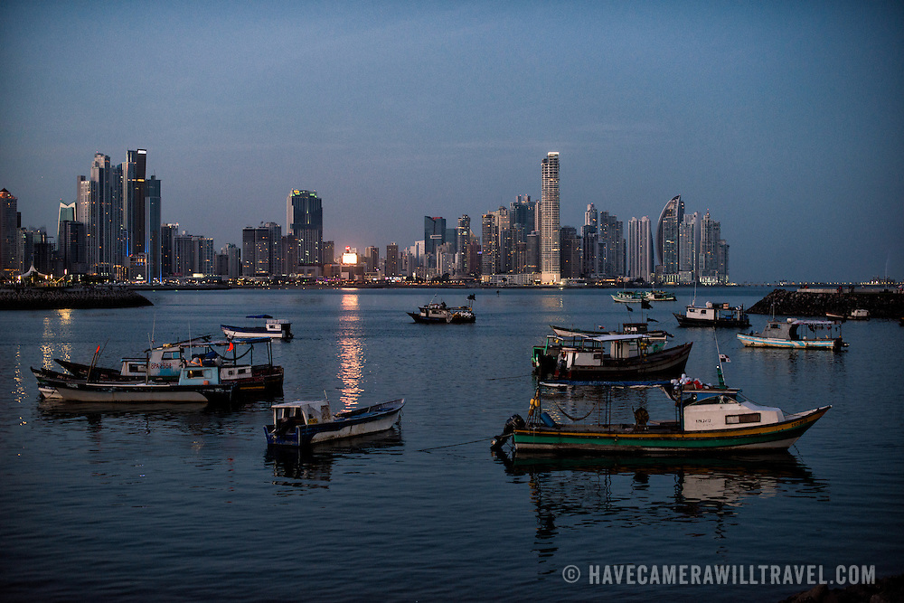 The modern skyscrapers of Punta Paitilla form a cityscape in the background, with the traditional wooden fishing boats of Panama City in the foreground. on the waterfront of Panama City, Panama, on Panama Bay.