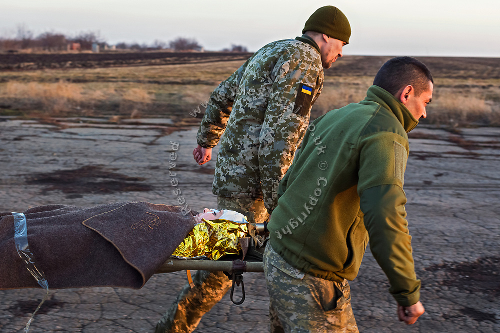 A woman is being evacuated to a helicopter in Bakhmut, a town in eastern Ukraine's conflict zone, carrying her to a better hospital in the city of Dnipropetrovsk. She was wounded when a sniper bullet hit the van she was travelling on in Zaitseve, close to the frontline, as she was bringing humanitarian aid to civilians alongside another volunteer, who was also injured.