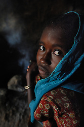"""Kadija's daughter Saidya, 11, prepares coffee inside their home near Barentu, Eritrea august 25, 2006. Kadija is a traditional birth assistant as well as a recipient of a donkey from the women's union """"Hamade"""". (Ami Vitale)"""
