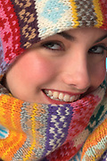 Close up of young woman wearing colorful knit winter scarf and cap