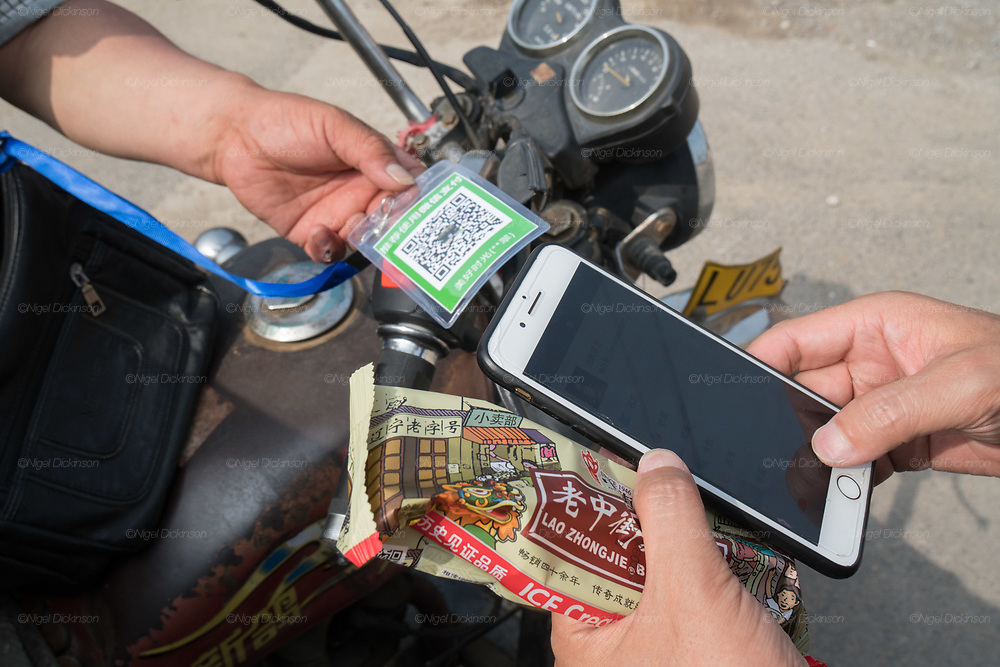 Buying an ice lolly or icecream from a street vendor on a motorbike on the road, using a cashless Wechat telephone application. The Chinese don't even use cash in the street anymore