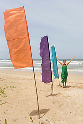 Colourful flags with happy woman on beach, Western Province, Sri Lanka