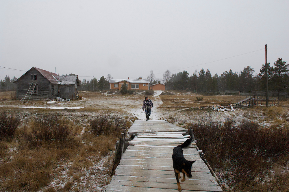 Uule Sara, 35, and dog Vota cross the bridge from his home. His grandparent's home (middleground left) remains but his modern day home supplants the old ways and more simple living. Despite the inhospitable Arctic climate reindeer herding has been the livelihood of the Sami for more than a thousand years, but amid the economic, technological, and environmental problems of modern society their indigenous culture must increasingly reconcile these radical changes in order to preserve age-old traditions, customs, and mores.