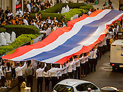 24 AUGUST 2015 - BANGKOK, THAILAND:    People carry a large Thai flag through central Bangkok during a memorial service for victims of the Erawan Shrine bombing. One week after the a bomb at the Erawan Shrine in the center of Bangkok killed dozens and hospitalized scores of people, police have not made any arrests. Police bomb sniffing dogs have been deployed to malls and markets around Bangkok. There was a large memorial service sponsored by businesses close the bomb site Monday evening.    PHOTO BY JACK KURTZ