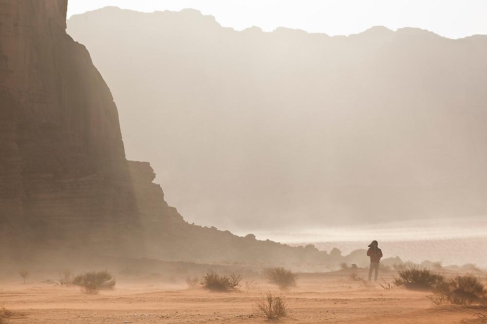 SeongRyeong Bak walks below high sandstone cliffs as the wind blows sand through the desert of Wadi Rum, Jordan.