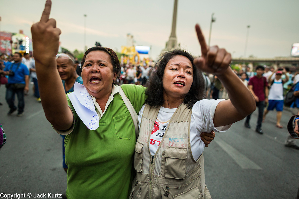 26 MAY 2014 - BANGKOK, THAILAND: Thai women wail and scream during a protest against the coup in Thailand at Victory Monument during a pro-democracy rally in Bangkok. About two thousand people protested against the coup in Bangkok. It was the third straight day of large pro-democracy rallies in the Thai capital as the army continued to tighten its grip on Thai life.   PHOTO BY JACK KURTZ