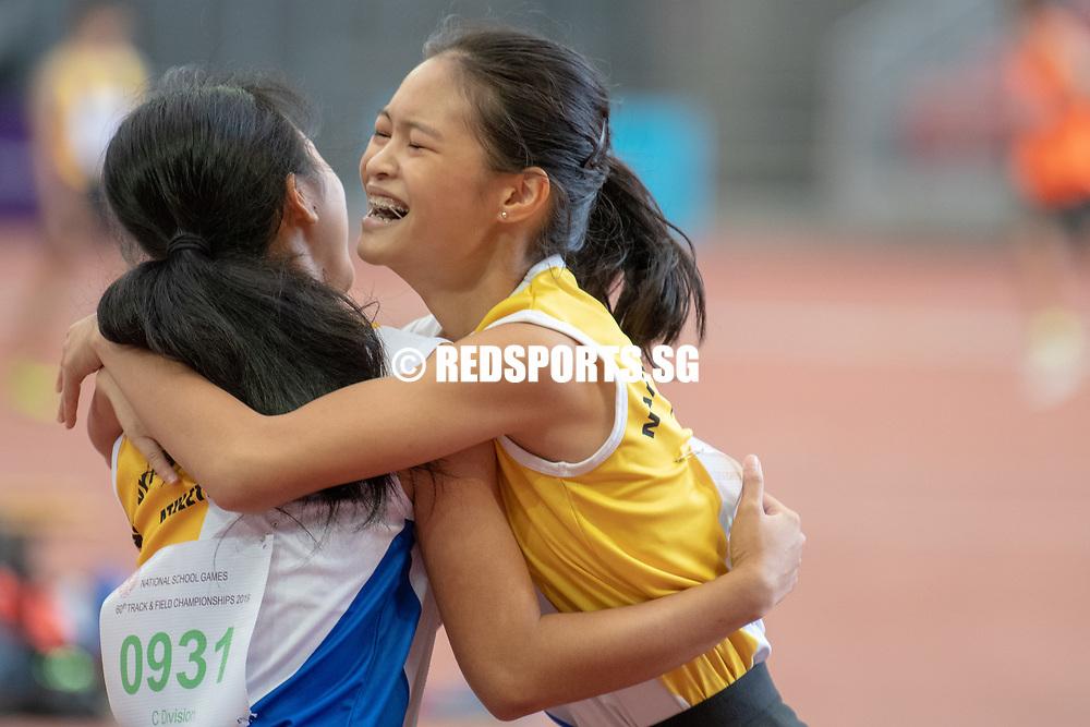 Eleana Goh (#925) embraces fellow NYGH runner Qiu Xinyu (#931) after the C Division Girls' 100m final. (Photo X © REDintern Jared Khoo)