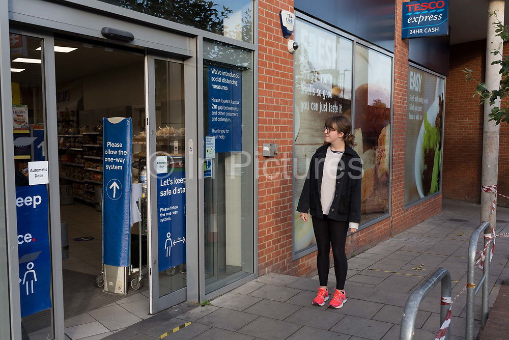 A young woman waits to be directed into a branch of a local Tesco Express supermarket in Herne Hill, during the UKs Conoriavirus pandemic lockdown, on 8th June 2020, in London, England.