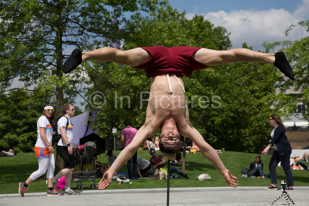 Acrobat from Gravity and Other Myths Circus, (Daniel Liddiard) practises his strength hand balancing act in Jubillee Gardens. The South Bank is a significant arts and entertainment district, and home to an endless list of activities for Londoners, visitors and tourists alike.