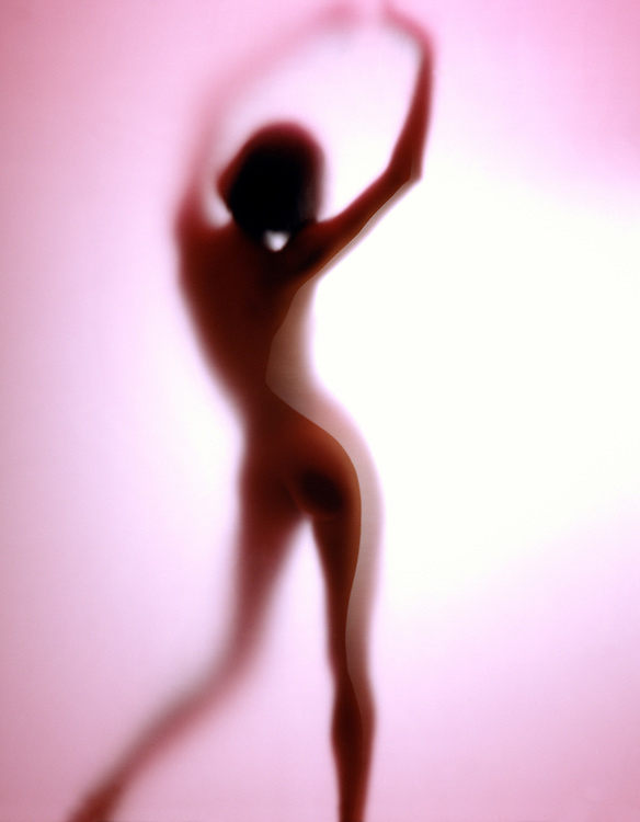 Graceful nude woman in silhouette with shadows behind translucent red matte material