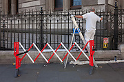 A workman paints black railings outside the National Portrait Gallery, on 23rd September 2016, in the central London borough of Westminster, England. An expandable barrier stretches across his working area of the pavement to avoid mishaps.
