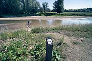 Nederland, Nijmegen, 30-7-2020 Bijna drooggevallen zijgeul van de Waal . Door de lage waterstand, laagwater,en de langdurige droogte is er geen aanvoer van water vanuit de rivier. Door het uitblijven van regen de afgelopen weken is de geul bijna leeg en opgedroogd . De geul is bedoeld als waterberging bij hoogwater . De Waal is het Nederlandse deel van de Rijn en de belangrijkste vaarroute van en naar Rotterdam en Duitsland . Foto: ANP/ Hollandse Hoogte/ Flip Franssen