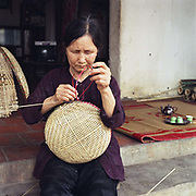 A woman weaving a bamboo basket in Tang Tien village, Bac Giang province, Vietnam. With Vietnam's growing population making less land available for farmers to work, families unable to sustain themselves are turning to the creation of various products in rural areas.  These 'craft' villages specialise in a single product or activity, anything from palm leaf hats to incense sticks, or from noodle making to snake-catching. Some of these 'craft' villages date back hundreds of years, whilst others are a more recent response to enable rural farmers to earn much needed extra income.