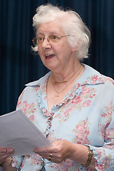 Elderly woman singing from song sheet,