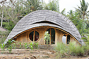 """Organic shaped house in vegetable garden<br /><br />The Green School (Bali) is one of a kind in Indonesia. It is a private, kindergarten to secondary International school located along the Ayung River near Ubud, Bali, Indonesia. The school buildings are of ecologically-sustainable design made primarily of bamboo, also using local grass and mud walls. There are over 600 students coming from over 40 countries with a percentage of scholarships for local Indonesian students.<br /><br />The impressive three-domed """"Heart of School Building"""" is 60 metres long and uses 2500 bamboo poles. The school also utilizes renewable building materials for some of its other needs, and almost everything, even the desks, chairs, some of the clothes and football goal posts are made of bamboo.<br /><br />The educational focus is on ecological sustainability. Subjects taught include English, mathematics and science, including ecology, the environment and sustainability, as well as the creative arts, global perspectives and environmental management. This educational establishment is unlike other international schools in Indonesia. <br /><br />Renewable energy sources, including solar power and hydroelectric vortex, provide over 50% of the energy needs of the school. The school has an organic permaculture system and prepares students to become stewards of the environment. <br /><br />The school was founded by John and Cynthia Hardy in 2008."""