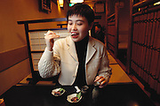 In a basement sushi bar in Tokyo, Japan, Mariko Urabe prepares to eat an inago, a grasshopper. She had never eaten one before this photograph and wasn't particularly interested in eating this one. The second small bowl of appetizers contains silkworm pupae. As is true in many countries, food preferences are culturally based and don't necessarily extend to the entire country. Image from the book project Man Eating Bugs: The Art and Science of Eating Insects.