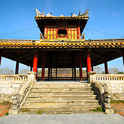 An ornate restored pagoda outside the walls of the Imperial City in Hue, Vietnam. A self-enclosed and fortified palace, the complex includes the Purple Forbidden City, which was the inner sanctum of the imperial household, as well as temples, courtyards, gardens, and other buildings. Much of the Imperial City was damaged or destroyed during the Vietnam War. It is now designated as a UNESCO World Heritage site.