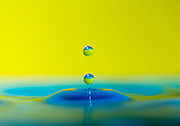 Water droplets fall on a coloured surface.