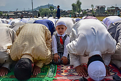 June 16, 2018 - Srinagar, Jammu and Kashmir, India - A child seen during the prayer. Kashmiri Muslims offer Eid prayers marking the festival of Eid al-Adha at eidgah in Srinagar summer capital of Indian administered Kashmir. Eid al-Fitr marks the end of the holy month of Ramadan, during which Muslims all over the world fast from Dawn To Dusk. (Credit Image: © Abbas Idrees/SOPA Images via ZUMA Wire)