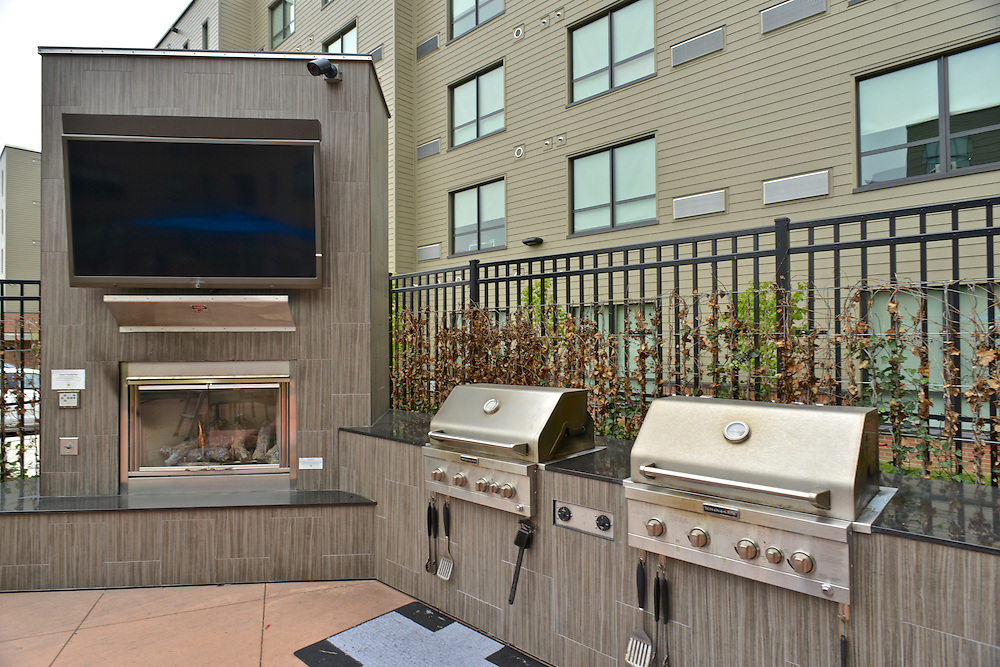 Grills, fireplace, and television in the outdoor patio at the 401 Lofts apartments.
