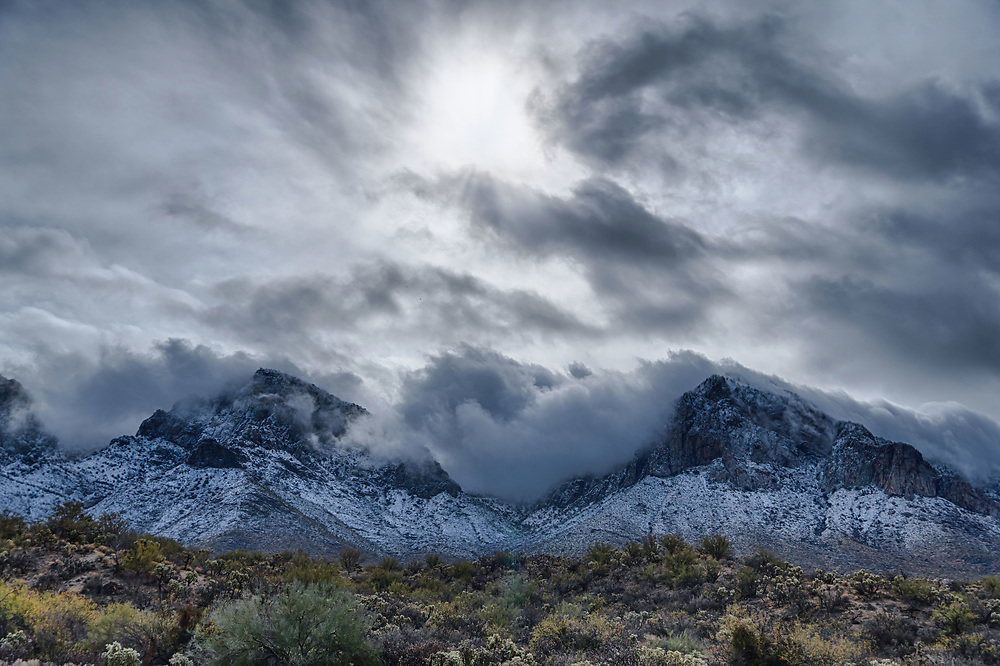 Clouds pour between two mountains like dry ice through a riverbed after a winter monsoon January 2021