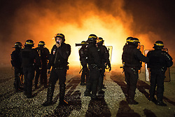 "© Licensed to London News Pictures . 23/10/2016 . Calais , France . Riot police at the Calais migrant camp known as "" The Jungle "" , in Northern France , on the evening before the start of the eviction and destruction of the camp . Photo credit: Joel Goodman/LNP"