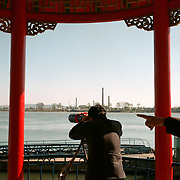 Dandong city, China, Sinuiju City, North Korea, 11-2003..Chinese tourists come to the edge of China to look at Sinuiju, a North Korean city just across the border. It reminds them of a time when they were poor...China help North Korea fight the Korean War in the 1950s and continue to have a defence treaty with the Stalinist country...Ruled by the messianic leader Kim Il Sung and his son Kim Jong Il since 1948, North Korea has stubbornly stuck to its juche (self-reliance) ideology and siege mentality, imposing one Stalinist economic plan after another. Floods, droughts and mismanagement in the 1990s plunged the country into a preventable famine, killing up to three million, or 13 percent of the population. It now depends heavily on Chinese aid...