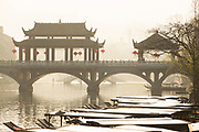 Traditional Chinese architecture of Wind Bridge above a river with boats, Fenghuang, Hunan Province, China