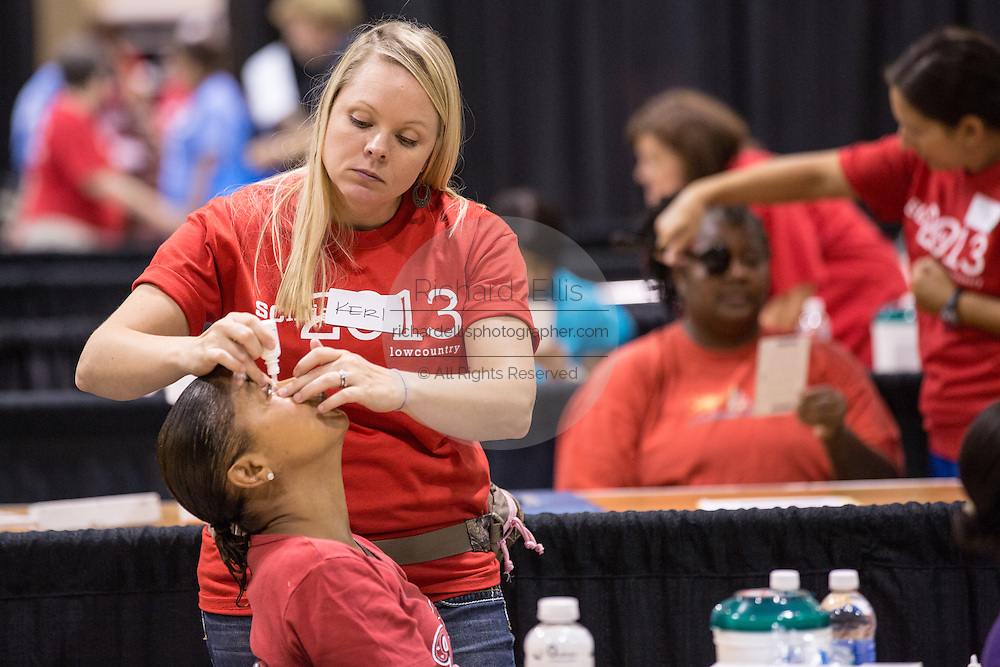 A volunteer medical technician prepares a patient for an eye exam during a free medical mission held by the SC Dental Association on August 23, 2013 in North Charleston, South Carolina. More than 1,000 people showed up to receive free dental and medical care.