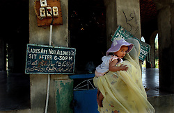 KASHMIR,INDIA: A Kashmiri Muslim woman and her child visit a Shiite shrine in Srinagar, the Indian held summer capital of the state of Jammu and Kashmir .  A sign reads that ladies are not allowed to enter the shrine after 6:30 p.m.  Islamic guerrillas have been fighting for independence of the Indian-controlled portion of Kashmir since 1989, but for the first time in 13 years, Kashmiris living in Srinagar have enjoyed a fragile peace and boom in tourism.