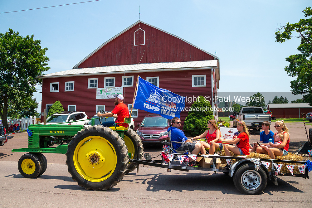 A man is seen driving a John Deere tractor with a Trump flag in the Independence Day Parade in Millville, Pennsylvania on July 5, 2021. (Photo by Paul Weaver)