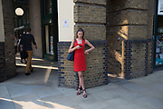 A woman wearing a red dress looks at her mobile phone on 19th June 2017 in London, United Kingdom.  From the series Our Small World, an observation of our mobile phone obsessions