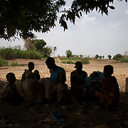 April 28, 2012 - Buram, Nuba Mountains, South Kordofan, Sudan: A Nuba family rests under the shade of a tree before continue the three to four day journey to a refugee camp in the neighbor South Sudan. Thousands of people have in the past months fled the bombardments and hunger in South Kordofan...Since the 6th of June 2011, the Sudan's Army Forces (SAF) initiated, under direct orders from President Bashir, an attack campaign against civil areas throughout the South Kordofan's province. Hundreds have been killed and many more injured...Local residents, of Nuba origin, have since lived in fear and the majority moved from their homes to caves in the nearby mountains. Others chose to find refuge in South Sudan, driven by the lack of food cause by the agriculture production halt due to the constant bombardments of rural areas. (Paulo Nunes dos Santos/Polaris)