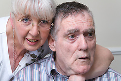 Woman showing affection whilst visiting her husband who has Alzheimer's Disease at the Nursing Home where he lives,