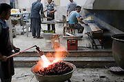 A worker ignites charcoal with a gas torch as other workers make and grill lamb kabobs in the kitchen of Talar Yazd Restaurant in Yazd, Iran.