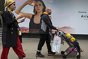 A mother and father with a child's buggy walk past a billboard ad featuring the face of a model advertising a perfume outside the retailer Debenhams on Oxford Street, on 16th April 2018, in London, England.