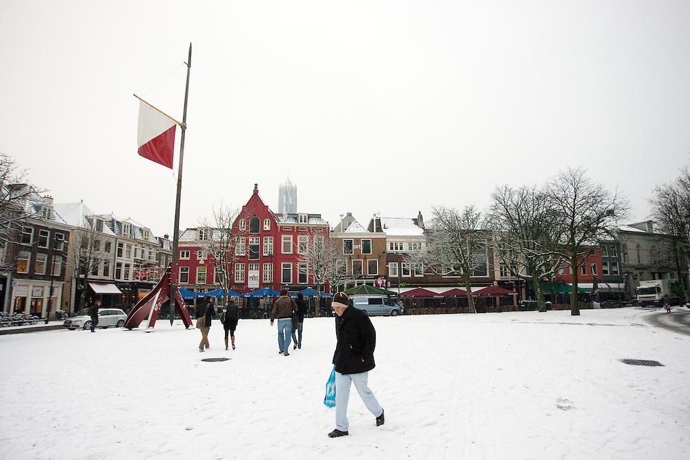 Een man loopt over de Neude door de sneeuw in Utrecht. In grote delen van Nederland is vandaag voor het eerst sneeuw gevallen