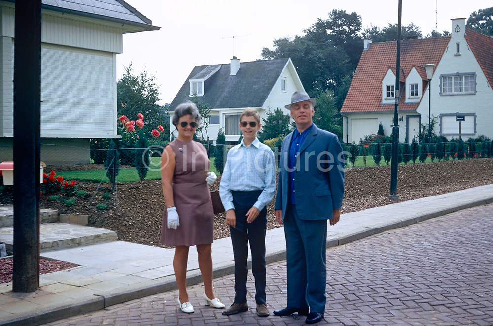 A middle-age mother and father with a teenage son pose for a photo outside their house in a Belgian suburb in the early 70s. Standing rather awkwardly in the street of modern cobbles, the three family members are ready to leave for a day out somewhere and we see their house's window on the left with its shutters lowered. The mother and wife wears white gloves, the husband and father wears a trilby hat - in the way people wore headwear in that bygone era.