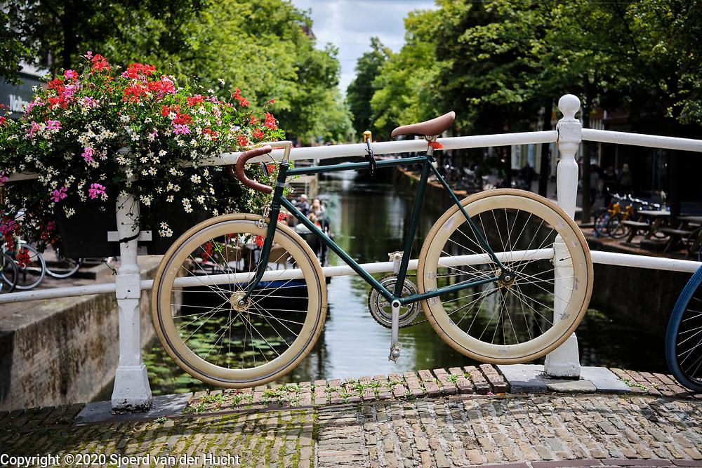 Sporty bicycle attached to a bridge above a canal in Delft.   Sportieve fiets vastgemaakt aan brug boven een gracht in Delft.