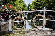 Sporty bicycle attached to a bridge above a canal in Delft. | Sportieve fiets vastgemaakt aan brug boven een gracht in Delft.