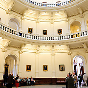 People meet on the markble floor under the massive dome of the Texas State Capitol building in Austin, Texas.