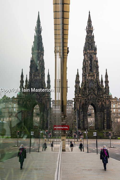 Edinburgh, Scotland, UK. 24 Feb 2021. As the UK and Scottish Governments outline rough timelines to ease the current lockdown , retailers and businesses remain close in UK city centres. Normally busy Princes Street remains eerily deserted with virtually all shops closed. Pic; Scott Monument reflected in shop window. Iain Masterton/Alamy Live News