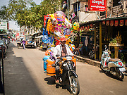 24 FEBRUARY 2015 - PHNOM PENH, CAMBODIA: A toy vendor rides his motorcycle past the White Building in Phnom Penh. The White Building, the first modern apartment building in Phnom Penh, originally had 468 apartments, and was opened the early 1960s. The project was overseen by Vann Molyvann, the first Cambodian architect educated in France. The building was abandoned during the Khmer Rouge occupation. After the Khmer Rouge were expelled from Phnom Penh in 1979, artists and dancers moved into the White Building. Now about 2,500 people, mostly urban and working poor, live in the building. Ownership of the building is in dispute. No single entity owns the building, some units are owned by their occupants, others units are owned by companies who lease out apartments. Many of the original apartments have been subdivided since the building opened and serve as homes to two or three families. The building has not been renovated since the early 1970s and is in disrepair. Phnom Penh officials have tried to evict the tenants and demolish the building but residents refuse to move out.  PHOTO BY JACK KURTZ