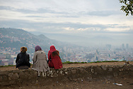 Three young women sit at the overlook at the Yellow Fortress, the city of Sarajevo in the distance