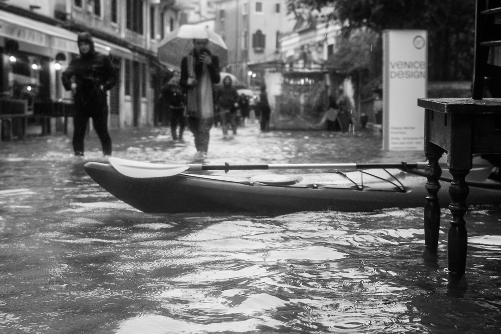 Venice, Italy. 29 October, 2018. A canoe is seen on a flooded street while people walks during the high tide on October 29, 2018, in Venice, Italy. This is a selection of pictures of different areas of Venice that the press has not covered, were resident live and every year they have to struggle with the high tide. Due to the exceptional level of the 'acqua alta' or 'High Tide' that reached 156 cm today, Venetian schools and hospitals were closed by the authorities, and citizens were advised against leaving their homes. This level of High Tide has been reached in 1979. © Simone Padovani / Awakening / Alamy Live News