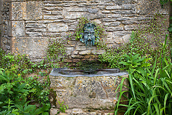 Bronze wall mask and spout in the Armillary Court at Snowshill Manor