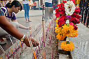 25 MARCH 2010 - BANGKOK, THAILAND: People light incense and pray at the Erawan Shrine in Bangkok. The Erawan Shrine (Thai: San Phra Phrom) is a Hindu shrine in Bangkok, Thailand that houses a statue of Phra Phrom, the Thai representation of the Hindu creation god Brahma. The Erawan Shrine was built in 1956 as part of the government-owned Erawan Hotel to eliminate the bad karma believed caused by laying the foundations on the wrong date. The hotel's construction was delayed by a series of mishaps, including cost overruns, injuries to laborers, and the loss of a shipload of Italian marble intended for the building. Furthermore, the Ratchaprasong Intersection had once been used to put criminals on public display. An astrologer advised building the shrine to counter the negative influences. The Brahma statue was designed and built by the Department of Fine Arts and enshrined on 9 November 1956. The hotel's construction thereafter proceeded without further incident.      PHOTO BY JACK KURTZ