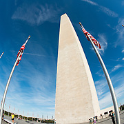 A fisheye lens view of the Washington Monument on a mostly clear day. The Washington Monument stands at over 555 feet (169 metres) at the center of the National Mall in Washington DC. It was completed in 1884 and underwent extensive renovations in 2012-13 after an earthquake damaged some of the structure.