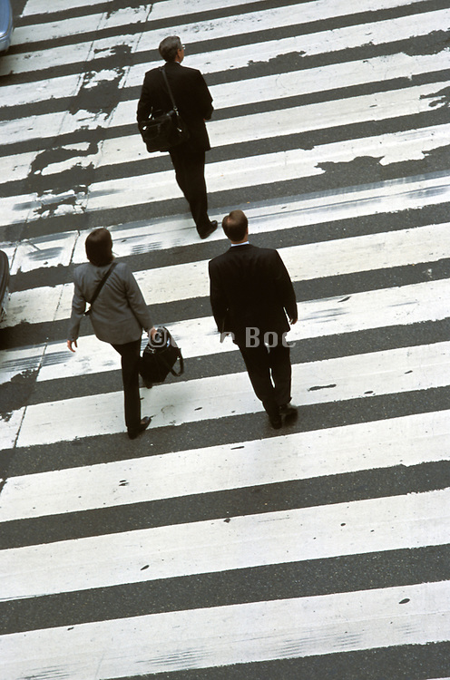 3 business people crossing a street