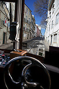 View from the inside of a Lisbon's nº28 yellow tram at Escolas Gerais street, on his way to Graça square, as part of the trip through the central, most historic region of the city.